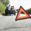 Couple Broken Down On Country Road With Hazard Warning Sign In F — Stock Photo