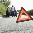 Royalty-Free Stock Photo: Family Broken Down On Country Road With Hazard Warning Sign In F