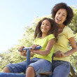 Mother And Daughter Riding On Seesaw In Park - Stock Photo