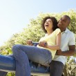 Portrait Of Young Couple Riding On SeeSaw In Park — Stock Photo