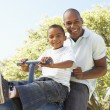 Father and Son Riding On SeeSaw In Park — Stock Photo