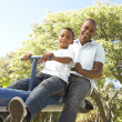Father and Son Riding On SeeSaw In Park — Stock Photo #4840330