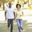 Portrait Of Young Couple Running Through Park — Stock Photo #4840331
