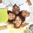 Portrait de famille heureuse, regardant vers le bas dans l'appareil photo dans le parc — Photo