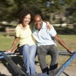 Young Couple Riding On Roundabout In Park - Stock Photo