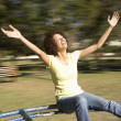 Young Woman Riding On Roundabout In Park — Stock Photo