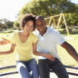 Young Couple Riding On Roundabout In Park — Stock Photo #4840375