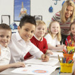 Group Of Primary Schoolchildren And Teacher Working At Desks In — Stock Photo