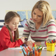 Stock Photo: Female Primary School Pupil And Teacher Working At Desk In Class