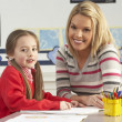 Female Primary School Pupil And Teacher Working At Desk In Class - Foto Stock