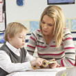 Stock Photo: Male Primary School Pupil And Teacher Working At Desk In Classro