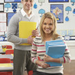 Portrait Of Male And Female Teacher Sitting At Desk In Classroom — Foto Stock