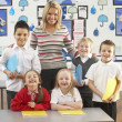 Portrait Of Group Of Primary Schoolchildren And Teacher Sitting — Stock Photo