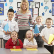 Portrait Of Group Of Primary Schoolchildren And Teacher Sitting - Stock Photo