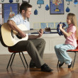 Male Teacher Playing Guitar With Pupil In Classroom — Stock Photo