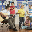 Male Teacher Playing Guitar With Pupils Having Music Lesson In C — Stok Fotoğraf #4840451