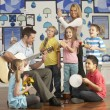 Teachers Playing Guitar With Pupils Having Music Lesson In Class — Foto Stock