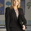 Portrait Of Female Primary School Teacher Standing In Classroom - Foto Stock