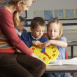 Female Teacher In Primary School Teaching Children To Tell Time — Stock Photo