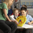 Stock Photo: Female Teacher In Primary School Teaching Children To Tell Time
