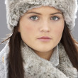 Young Woman Wearing Warm Winter Clothes And Fur Hat  In Stu - Zdjęcie stockowe