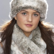 Young Woman Wearing Warm Winter Clothes And Fur Hat  In Stu - 图库照片