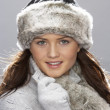 Young Woman Wearing Warm Winter Clothes And Fur Hat  In Stu - Stock Photo