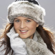 Royalty-Free Stock Photo: Young Woman Wearing Warm Winter Clothes And Fur Hat  In Stu
