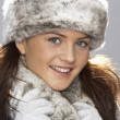 Stock Photo: Young WomWearing Warm Winter Clothes And Fur Hat In Stu