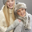 Two Fashionable Teenage Girls Wearing Cap And Knitwear In Studio In Front O - Stock fotografie