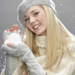 Teenage Girl Wearing Warm Winter Clothes And Hat Holding Snow In Studio - Foto Stock
