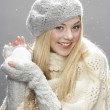 Teenage Girl Wearing Warm Winter Clothes And Hat Holding Snow In Studio - Stok fotoğraf