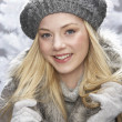 Fashionable Teenage Girl Wearing Cap And Fur Coat In Studio With Snow - Foto Stock
