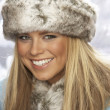 Studio Portrait Of Young Woman Wearing Fur Hat And Coat - Stock Photo