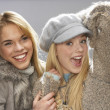 Two Fashionable Teenage Girls Wearing Cap And Knitwear In Studio - Stock Photo