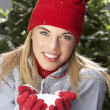 fashionable teenage girl wearing cap and knitwear holding snowball in studi — Stock Photo
