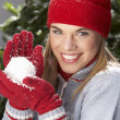 Fashionable Teenage Girl Wearing Cap And Knitwear Holding Snowball In Studi - Foto Stock