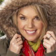 Royalty-Free Stock Photo: Fashionable Woman Wearing Parka Coat And Scarf In Studio In Front Of Christ