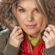 Fashionable Woman Wearing Parka Coat And Scarf In Studio In Front Of Christ - Stockfoto