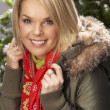 Fashionable Woman Wearing Parka Coat And Scarf In Studio In Front Of Christ - Foto Stock