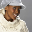 Fashionable Woman Wearing Knitwear And Cap In Studio In Front Of Christmas - Zdjęcie stockowe