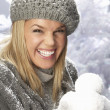 Fashionable Woman Wearing Cap And Knitwear Holding Snowball In Studio In Fr - Foto de Stock  