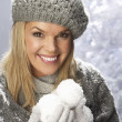 Fashionable Woman Wearing Cap And Knitwear Holding Snowball In Studio In Fr - Zdjęcie stockowe