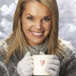 Young Woman Drinking Hot Drink Wearing Knitwear In Studio In Front Of Chris - Foto Stock