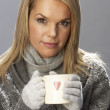 Young Woman Drinking Hot Drink Wearing Knitwear In Studio In Front Of Chris — Stock Photo