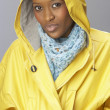 Stock Photo: Young WomWearing Yellow Raincoat In Studio
