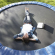 Young Man Relaxing On Trampoline With Laptop — Stock Photo