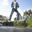 Young Man Jumping On Trampoline Caught In Mid Air — Stock Photo