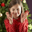Young Girl Crossing Fingers In Front Of Christmas Tree - Stock Photo