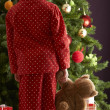 Oung Girl Standing With Teddy Bear In Front Of Christmas Tree — Stok fotoğraf
